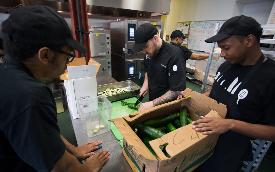 Chef trainer Travis Torsell, 38, of the South Side, shows students James Dreher (left), 25, and Recardo Williams, 29, how to properly cut zucchini. (Photo by John Hamilton/PublicSource)