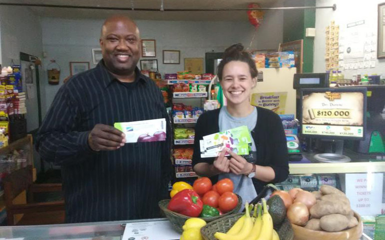 Carl Lewis, owner of Carl's Cafe in Wilkinsburg, and Emily Schmidlapp of the nonprofit Food Trust hold Food Bucks. Food Bucks can be used to purchase fresh fruits and vegetables. (Photo by Sarah Boden/90.5 WESA)