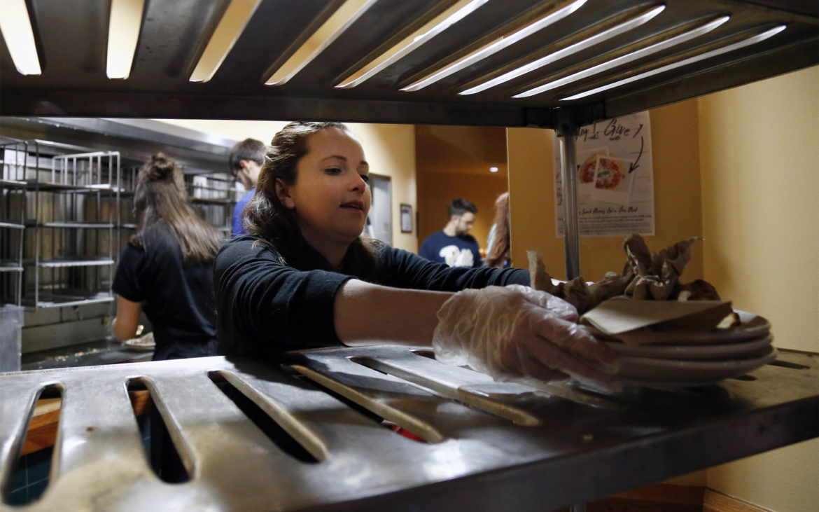 """University of Pittsburgh senior Jessica Nygard collects plates of discarded food during a """"waste audit"""" in the Market Central dining hall on Feb. 14, 2018. (Photo by Ryan Loew/PublicSource)"""