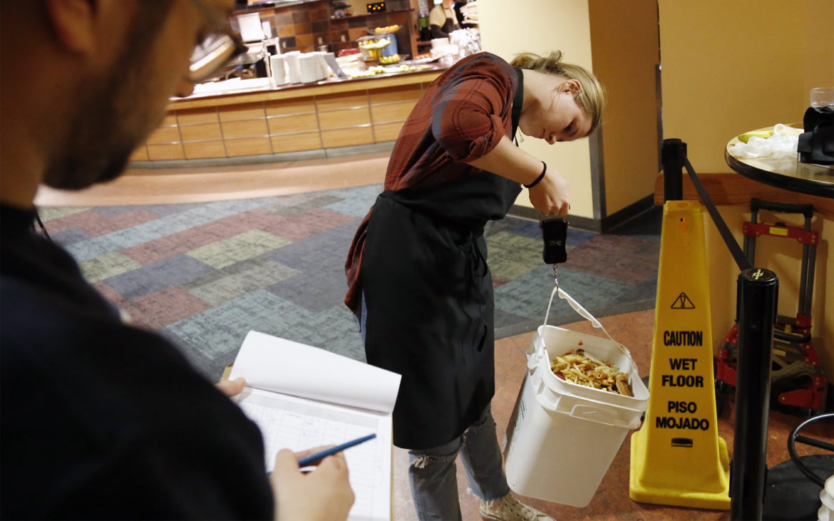 """Hope Kelly, a University of Pittsburgh junior and food waste intern for Pitt Dining, weighs food waste collected during a """"waste audit"""" while Nick Goodfellow records the weight. Goodfellow serves as the sustainability coordinator for the University of Pittsburgh's dining services. (Photo by Ryan Loew/PublicSource)"""