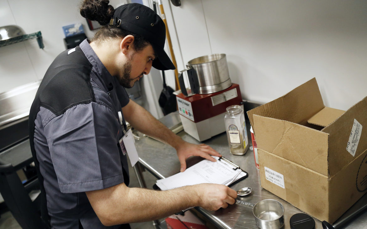 Retail cook Marven Khalid looks over a production sheet in a food prep area at the Brickside Eatery at UPMC Montefiore on March 5, 2018. (Photo by Ryan Loew/PublicSource)