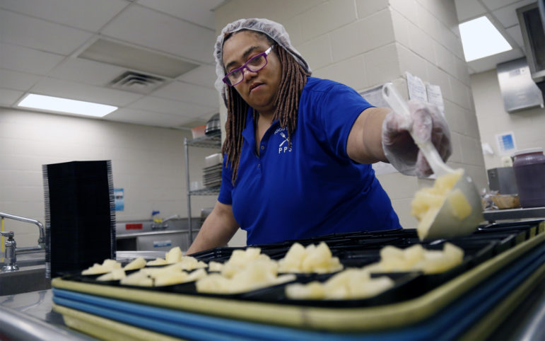 Food service worker Lisa Jackson spoons canned pineapple into 5-ounce containers during lunch prep at Pittsburgh Westinghouse Academy 6-12 on Feb. 1, 2018. (Photo by Ryan Loew/PublicSource)