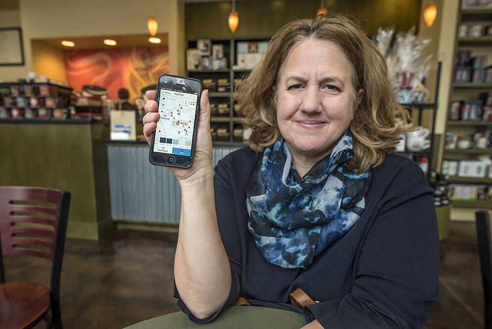 Lisa Minetti has asthma and plans to leave Pittsburgh because of the bad air quality. On her phone she has the Smell Pittsburgh app from CMU's Create lab on which users report air quality issues. (Photo by Teake Zuidema/PublicSource)