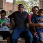 Muffy Mendoza and her three sons — (left to right) Mackell, Jair and Phillip — sit for a portrait on the front porch of their home in Sheridan. (Photo by Maranie R. Staab/PublicSource)