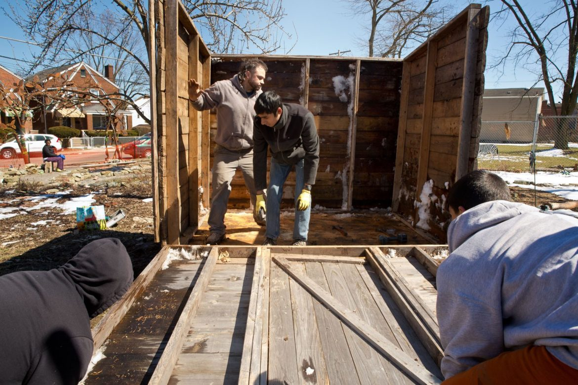 Larimer resident Ken Bey, Ben Ledewitz, East Liberty Presbyterian Church youth group member Ashwin Srinivasan and Larimer resident Juan Angel (left to right) work on building a shed in the African Healing Garden on March 25, 2018. (Photo by Heather Mull/PublicSource)