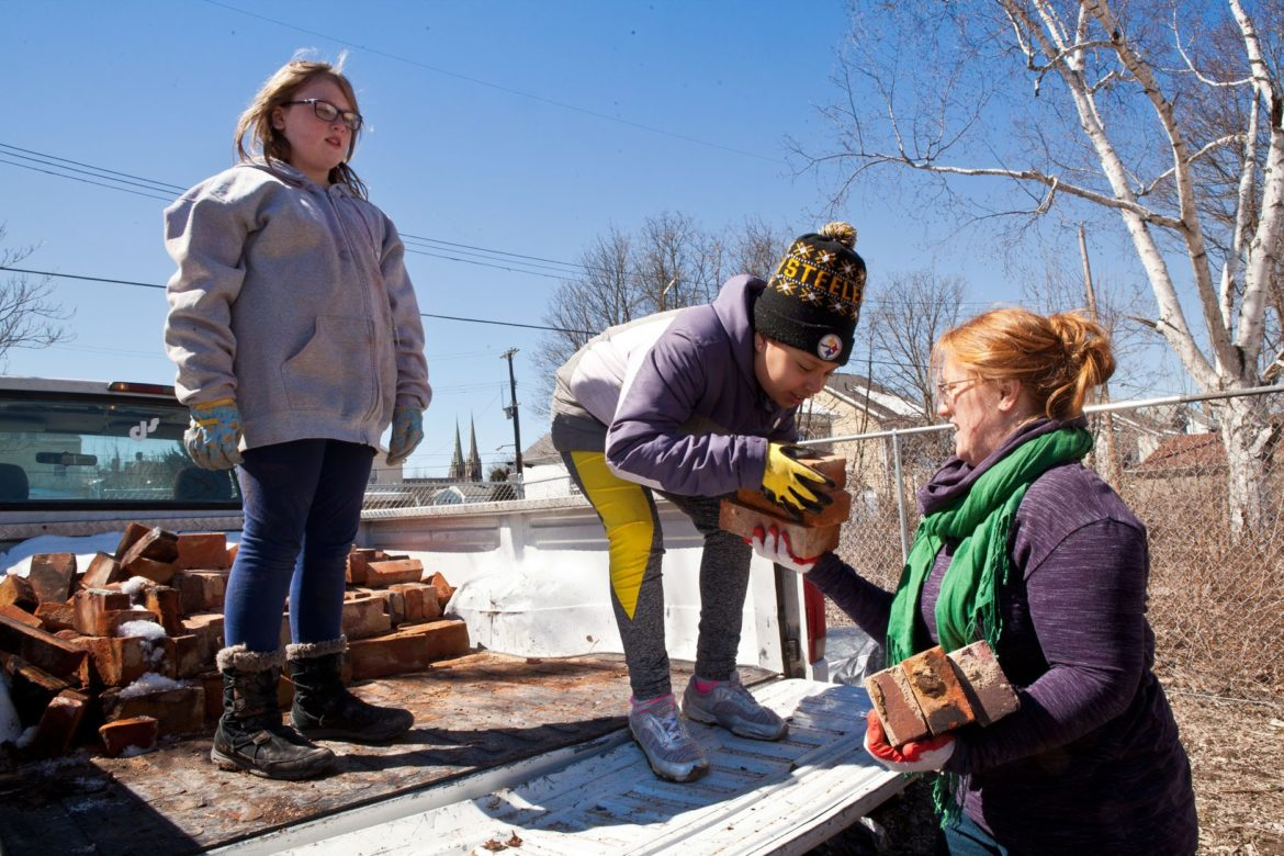 In March, a youth group from East Liberty Presbyterian Church volunteered time working in the garden. Here, Emmaline Thompson (left) works alongside Juliette Young (center), as she hands bricks to Sara Hackett, coordinator of Christian Education and Youth Ministries for the church. (Photo by Heather Mull/PublicSource)