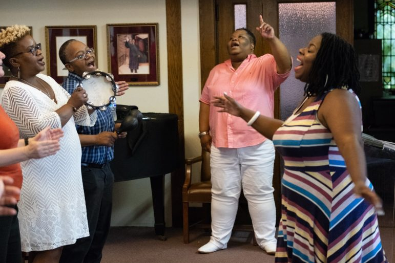 Rev. Shanea Leonard, the pastor of Judah Fellowship Christian Church, sings along with the congregation during worship. Anita Levels directs the worshipers in song. (Photo by Terry Clark/PublicSource)