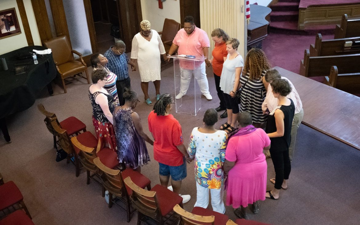 Rev. Shanea Leonard leads worshipers in a prayer circle during Saturday evening services. (Photo by Terry Clark/PublicSource)