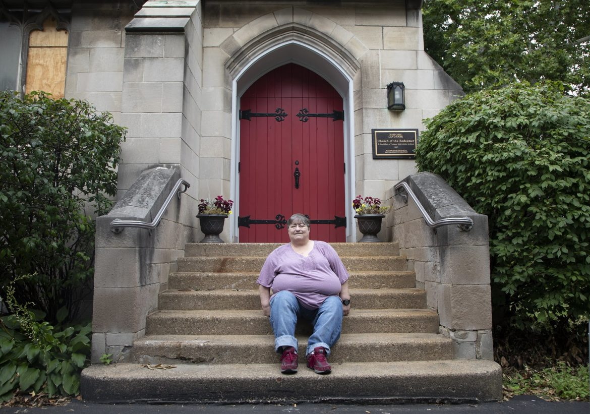 Donna Bachner, 61, sits on the stairs of the Church of the Redeemer in Squirrel Hill for a portrait. Bashner said she stayed with the church because of its acceptance to all communities and people. (Photo by Kat Procyk/PublicSource)