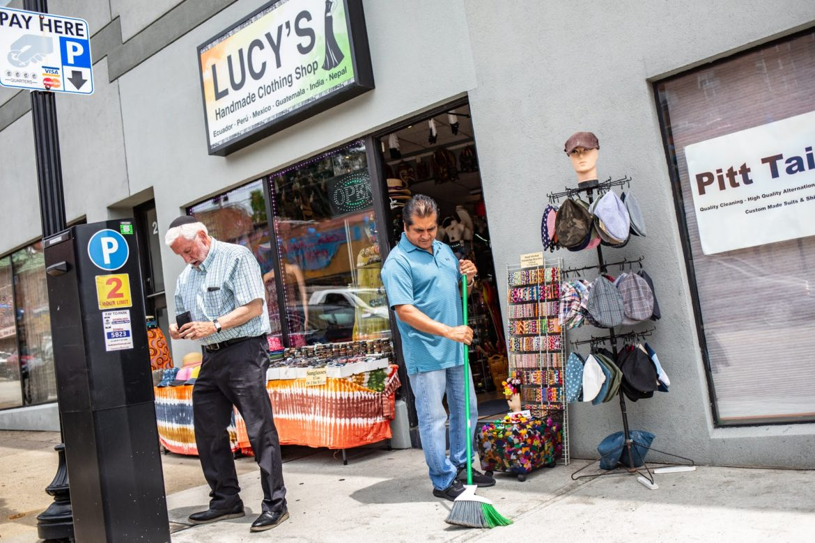 Owner Martin Villalba sweeps the sidewalk in front of Lucy's Handmade Clothing Shop on 2023 Murray Avenue in Squirrel Hill as a motorist pays for parking at Pittsburgh Parking Authority kiosk. (Photo by John Altdorfer/PublicSource)