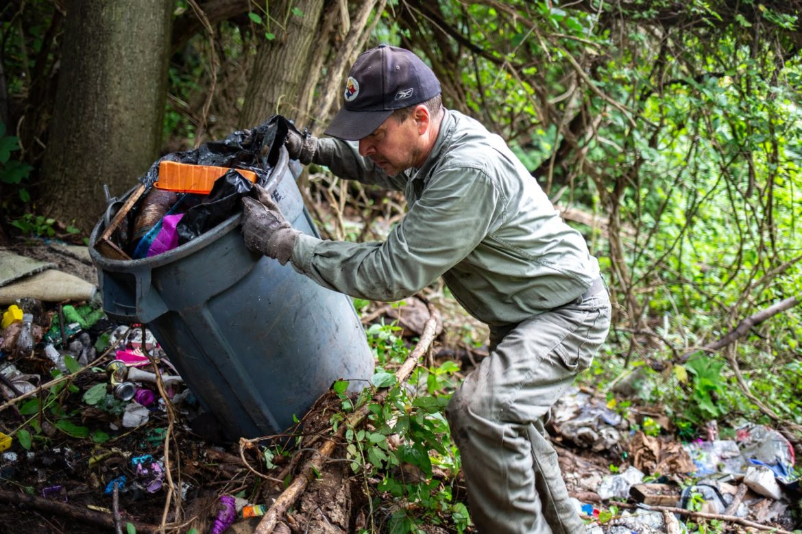 Allegheny CleanWays' DumpBuster crew leader Al Chernov hauls a garbage can of discarded items collected at an illegal hillside dump site along North Wheeler Street in Homewood. (Photo by John Altdorfer/PublicSource)