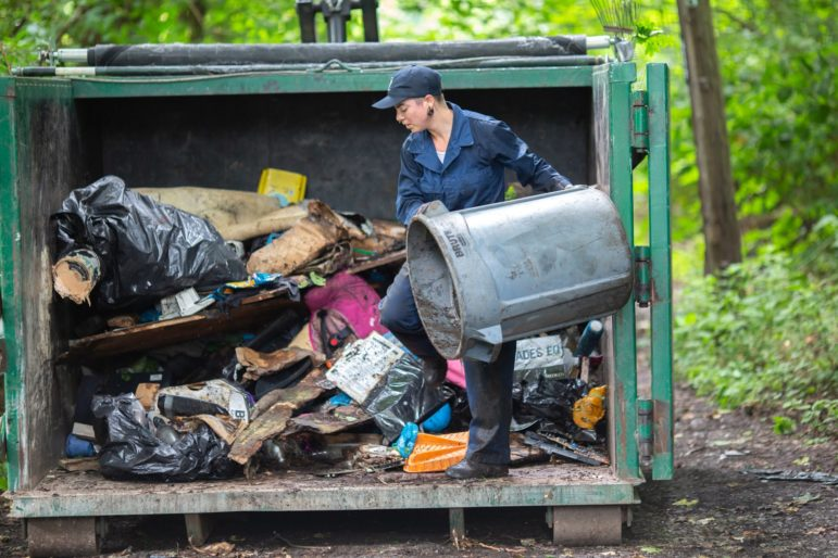 Crew member Dani Kramer empties a garbage can of discarded items she collected at an illegal hillside dump site along North Wheeler Street in Homewood. (Photo by John Altdorfer/PublicSource)