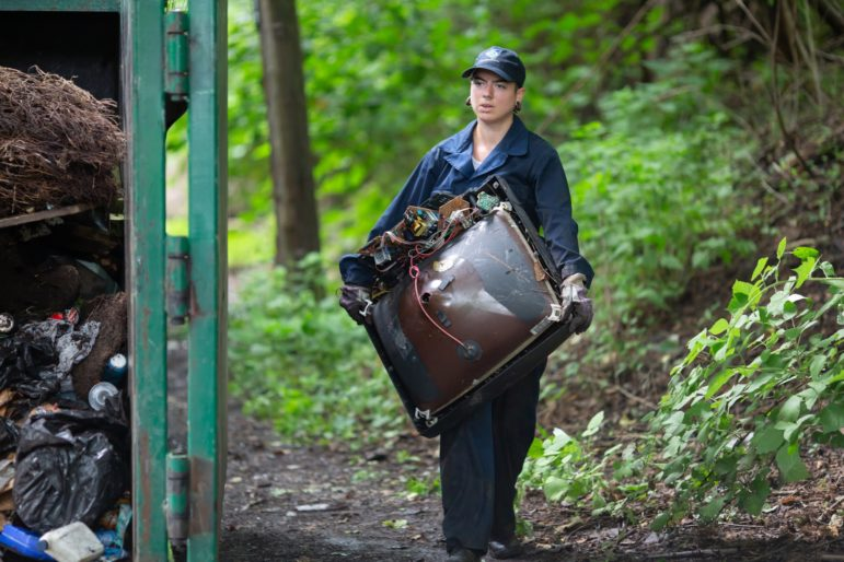 Crew member Dani Kramer carries a discarded cathode ray tube from an analog television to a garbage bin at an illegal hillside dump site along North Wheeler Street in Homewood. (Photo by John Altdorfer/PublicSource)