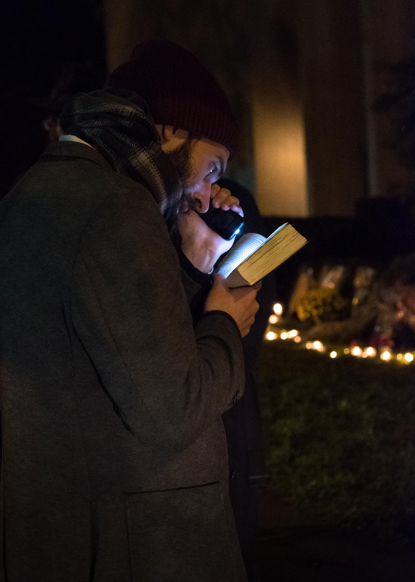 A man chants verses from the Torah in front of a shrine of lit candles on Shady Avenue outside the Tree of Life synagogue.