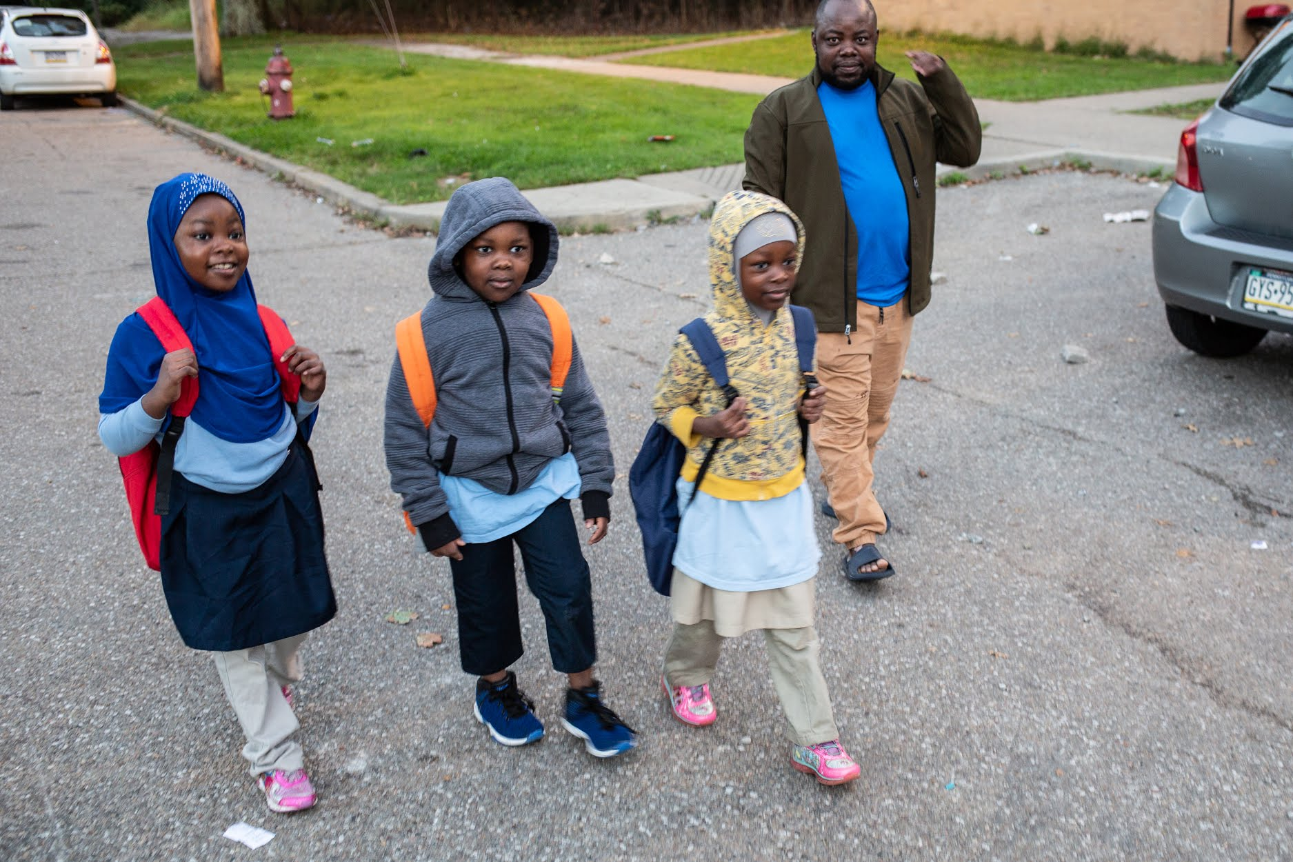 Juma Mkomwa walks his children, Arbay, Mohamed and Halima, to the school bus stop near the family's home in Northview Heights on Oct. 10. (Photo by John Altdorfer/PublicSource)
