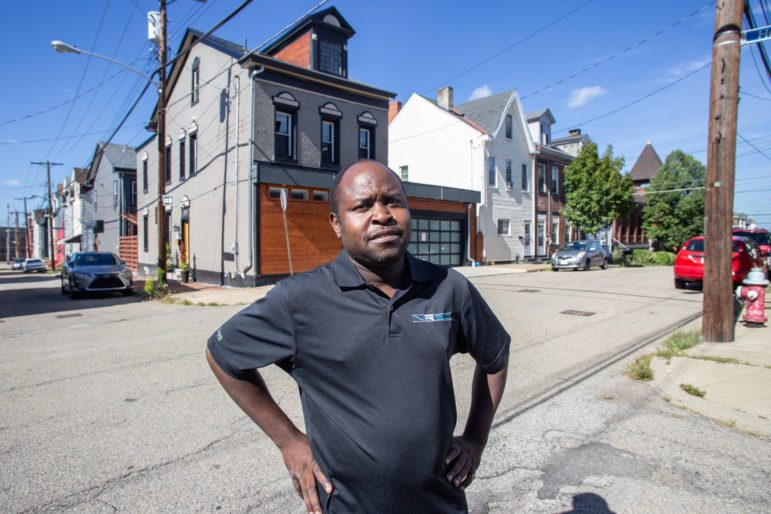 Omar Muya revisits his former home at 39th and Howley streets in Lawrenceville. He and his family had to move when the building owner sold to a redeveloper. (Photo by John Altdorfer/PublicSource)