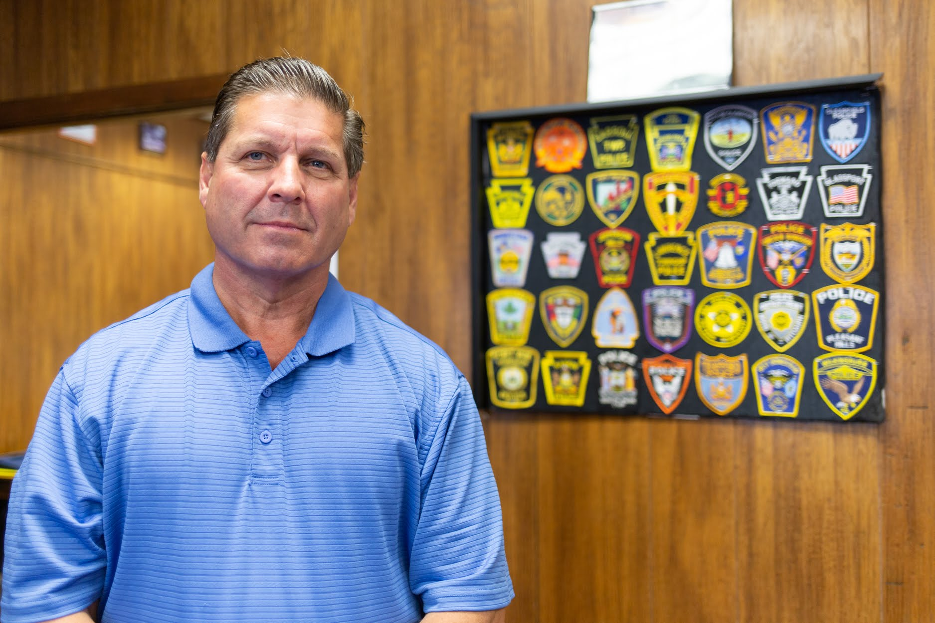 Carl Bailey, secretary-treasurer and principal officer of Teamsters Local 205, stands in his White Oak office in front of a collection of emblems representing some of the local police forces represented by the union. (Photo by John Altdorfer/PublicSource)