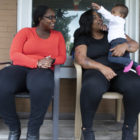 Montia Brock (left) and Carissa Ashby (right) spend time with Ashby's daughter on the front porch of Ashby's Swissvale home. Brock, a community health worker and perinatal health policy specialist from Healthy Start, conducts home visits to Ashby. (Photo by Kat Procyk/PublicSource)