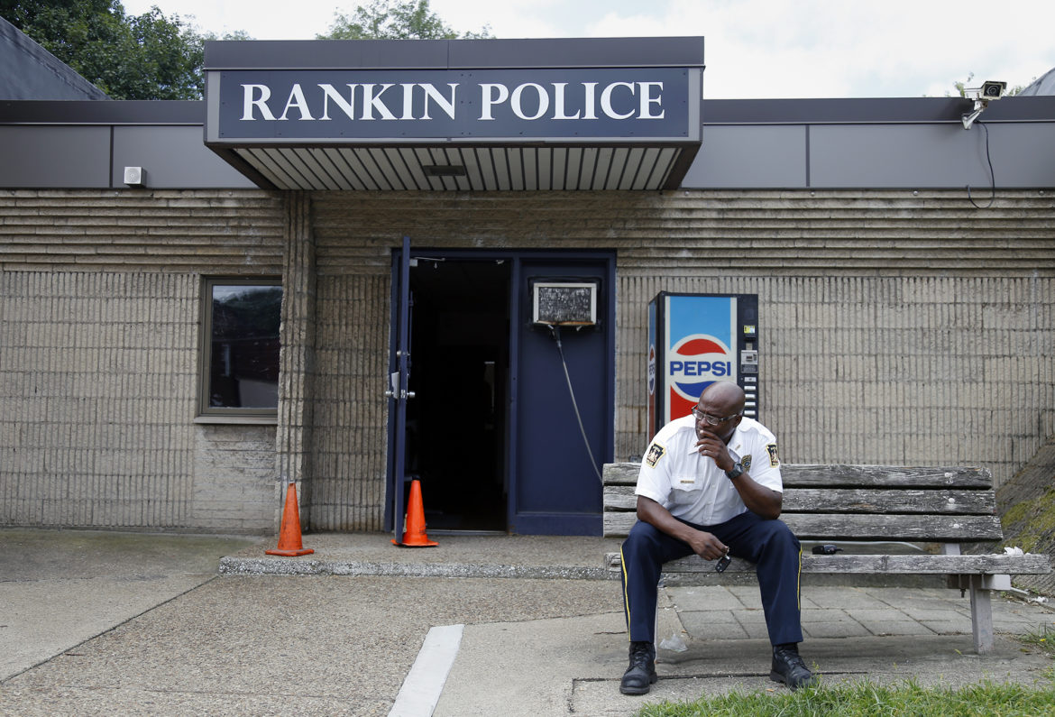 "In Rankin, Chief Ryan Wooten sits outside the borough's police headquarters. He asks himself every day: ""How do I police this community with no funds?"" (Photo by Ryan Loew/PublicSource)"