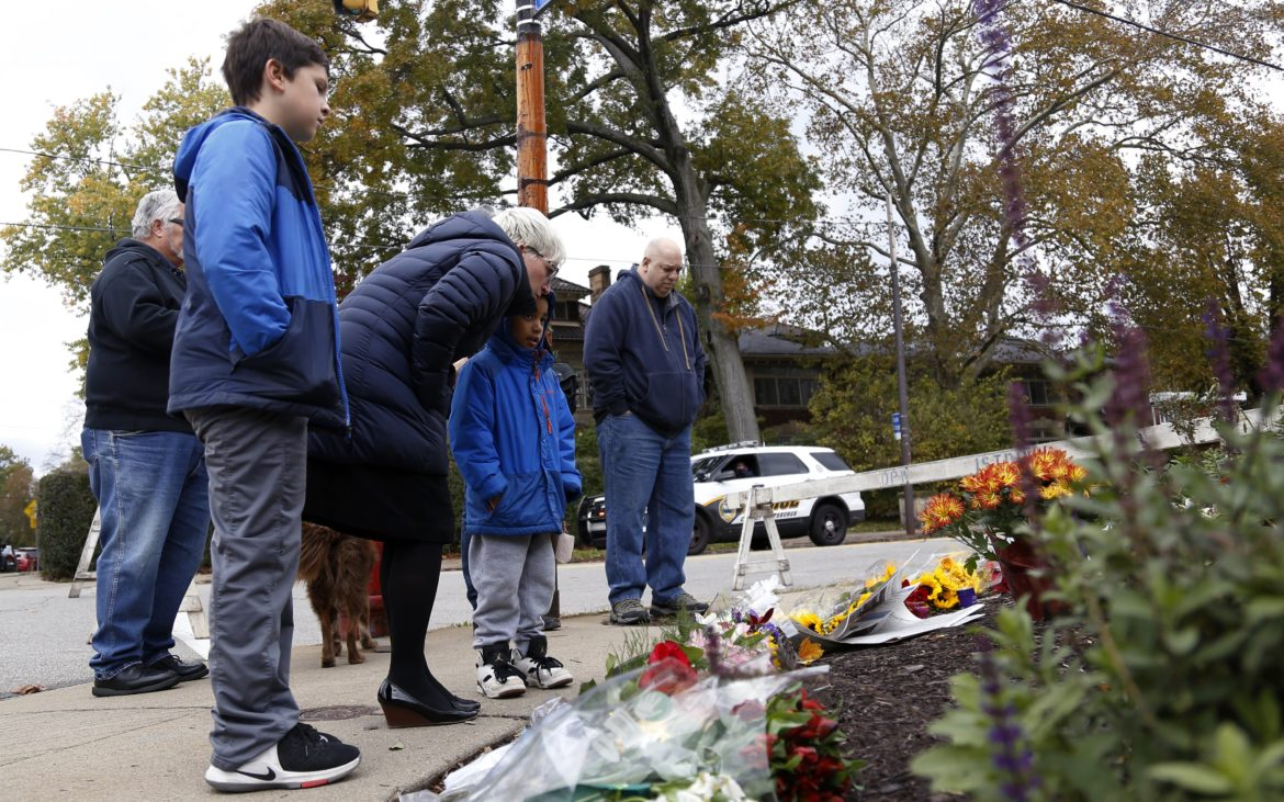 People visit a memorial site at the intersection of Shady Avenue and Northumberland Street in Squirrel Hill on Oct. 29. (Photo by Ryan Loew/PublicSource)