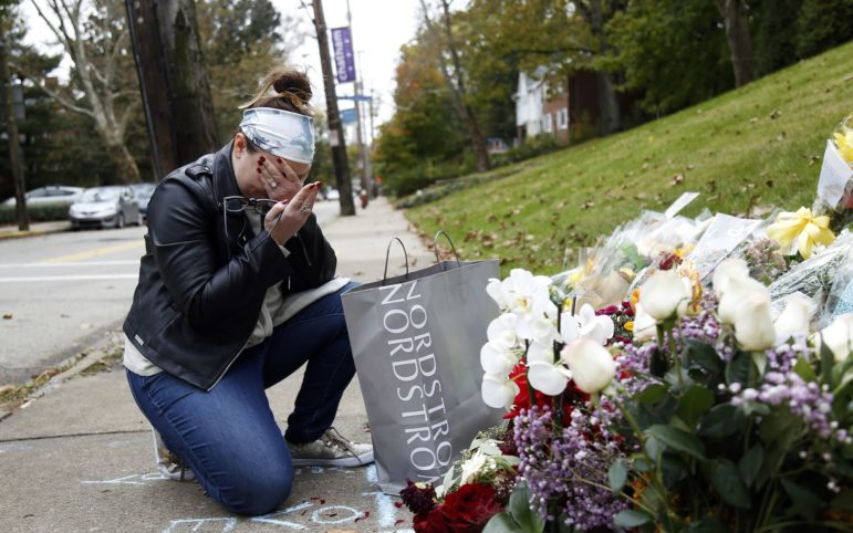 Samantha Ecker, 34, of Williamsport, Pa., kneels beside a memorial site at the intersection of Wilkins and Murray avenues last Monday. On Oct. 27, 11 people were killed at the Tree of Life synagogue in Squirrel Hill. Ecker, who celebrated her wedding downtown the same day, laid bouquets from her wedding at the site. (Photo by Ryan Loew/PublicSource)