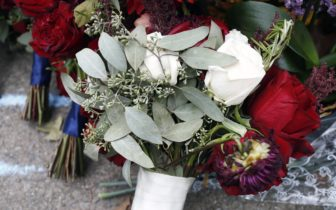 Samantha Ecker, who celebrated her wedding last Saturday, laid her wedding bouquet and three of her bridesmaids' bouquets at a memorial site at the intersection of Wilkins and Murray avenues. (Photo by Ryan Loew/PublicSource)