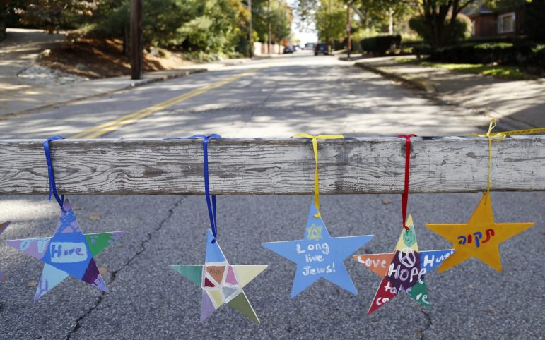 Stars hang from a road block on Wilkins Avenue in Squirrel Hill, down the street from the Tree of Life synagogue. (Photo by Ryan Loew/PublicSource)