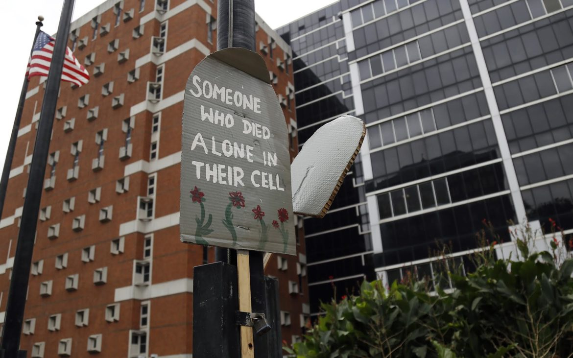 "A sign attached to a flagpole outside the Allegheny County Jail reads, ""Someone who died alone in their cell."" (Photo by Ryan Loew/PublicSource)"