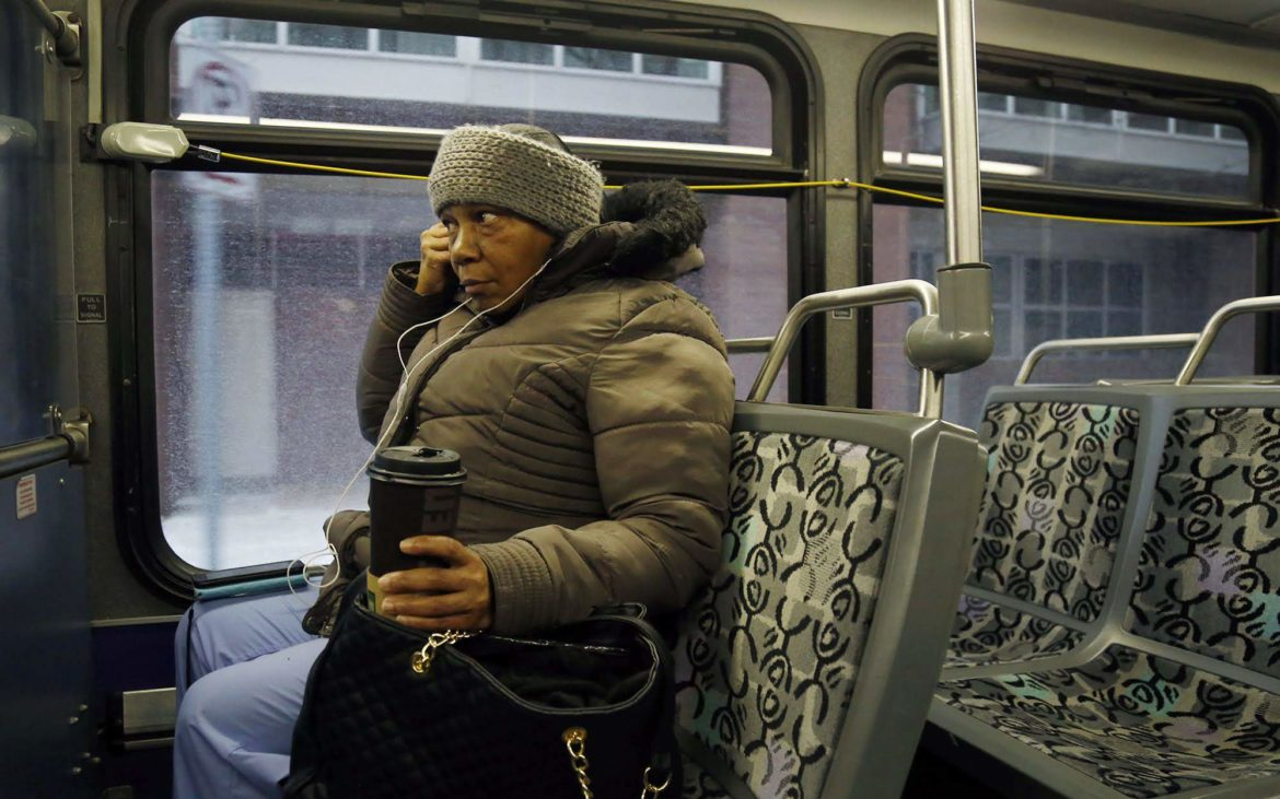 Alandia Heard rides a Port Authority bus from downtown to a home on the North Side at the start of her work day on Nov. 28. Heard works as a personal care assistant and spends about two hours riding each day. (Photo by Ryan Loew/PublicSource)