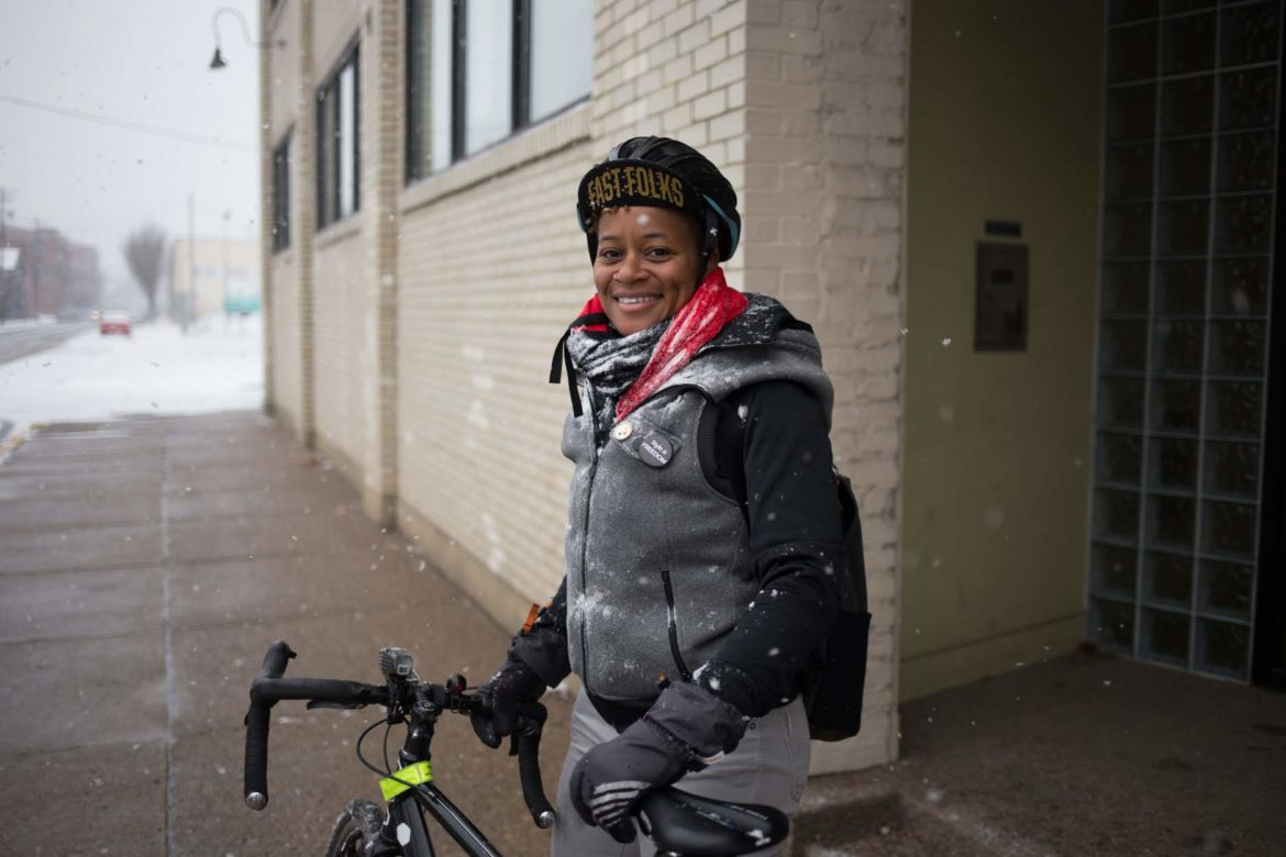 "Shequaya Bailey arrives at her job at Grounded Strategies in Homewood on Nov. 28. ""I know that sounds crazy because I've been hit a couple times, but I just am happier when I'm commuting on my bike. I'm just way more chill and I have this whole better outlook."" (Photo by John Altdorfer/PublicSource)"