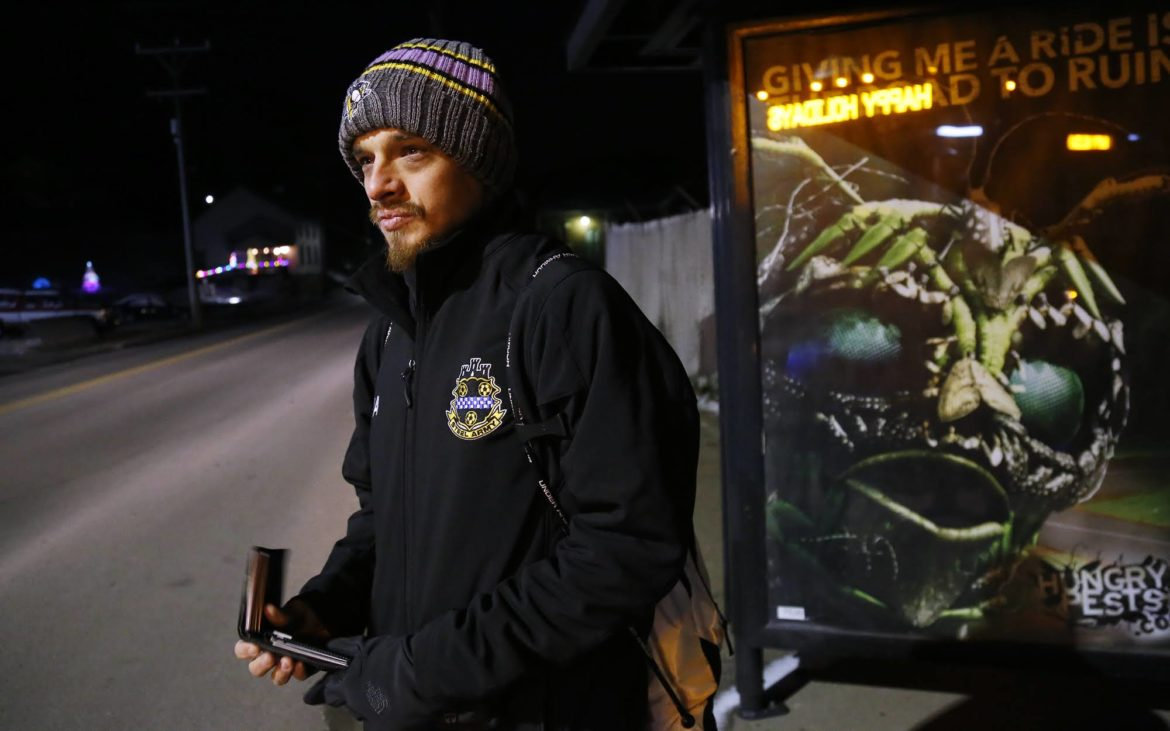 New Eagle resident Jesse Acton waits for a bus in the early morning hours of Nov. 29 to on his way to work. In addition to a job at Segway Pittsburgh, Acton currently does seasonal work at South Hills Village mall. On this morning that job started at 7 a.m., so he was catching the bus at 6 a.m. (Photo by Ryan Loew/PublicSource)