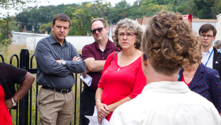 Joey Vallarian and Tim Prevost, of ALCOSAN (left) and Ryan Quinn, the project lead for PWSA (right), listen to Aly Shaw of Pittsburgh United describe a small green infrastructure project that could eventually send its water to the Little Negley Run. (Photo by Oliver Morrison/PublicSource)