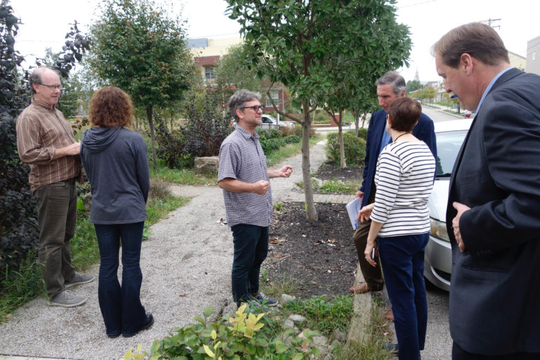 Ian Lipsky (center) talked to ALCOSAN board members and officials about the permeable sidewalk at a small green infrastructure project. (Photo by Oliver Morrison/PublicSource)