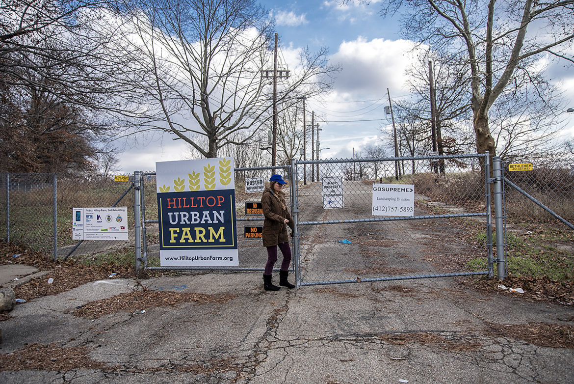 Sarah Baxendell unlocks the gates of the Hilltop Urban Farm in St. Clair. The farm is planned to be the largest urban farm in the country. (Photo by Teake Zuidema/PublicSource)