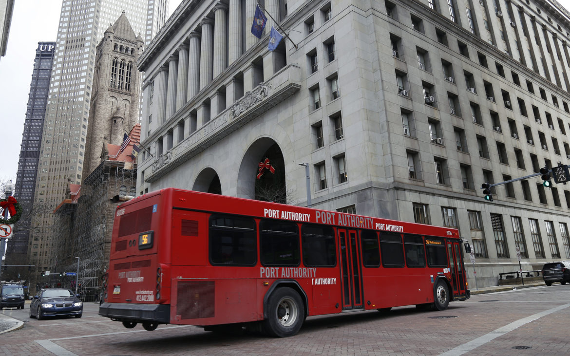A red Port Authority bus moves along Fourth Avenue in downtown Pittsburgh.