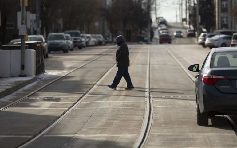 A pedestrian crosses the street in Beechview. (Photo by Kat Procyk/PublicSource)