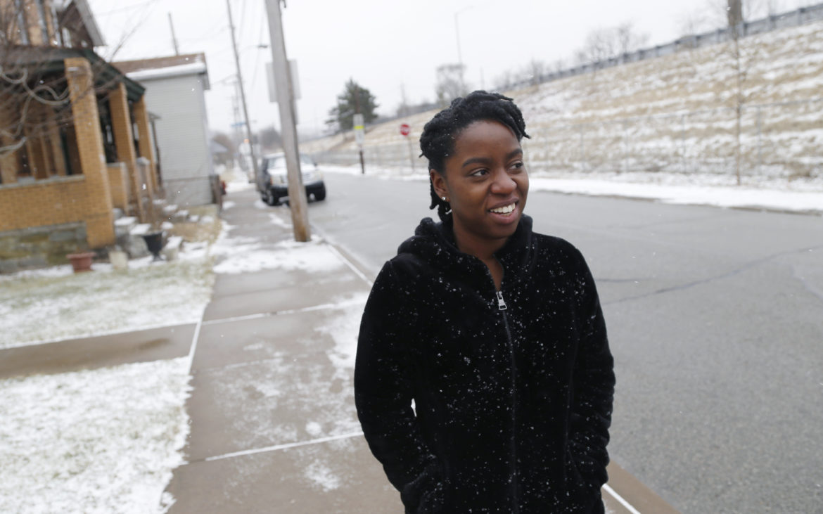 NaTisha Washington, green initiative coordinator for Operation Better Block, walks along Finance Street in Homewood. (Photo by Ryan Loew/PublicSource)