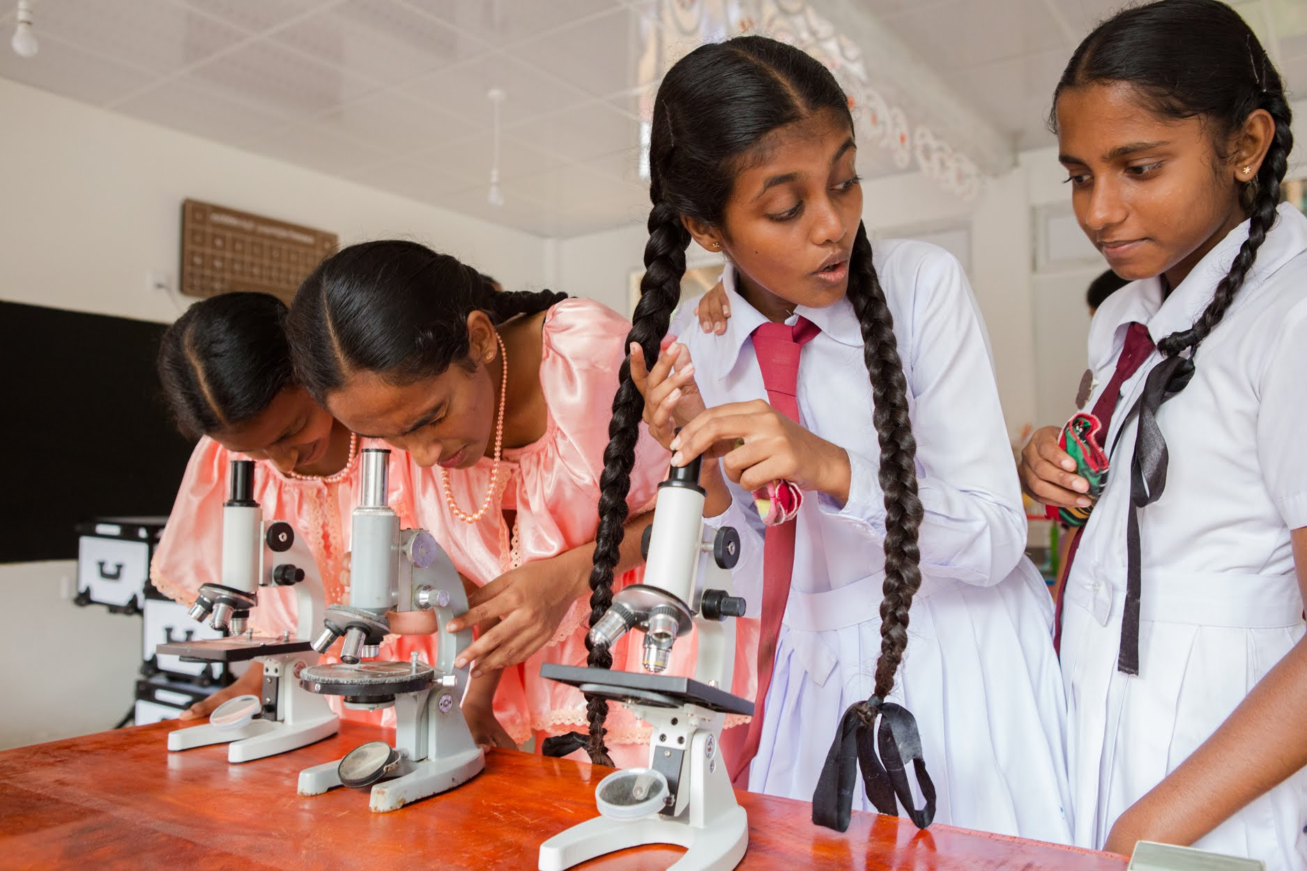 Schoolgirls at Palpita School test out the new microscopes in the science lab building. With a brand new interior, floors, and furniture, the science lab is the only classroom at the school that is enclosed by windows; all other classrooms at the school are contained inside open air pavilions with just screening covering the windows.