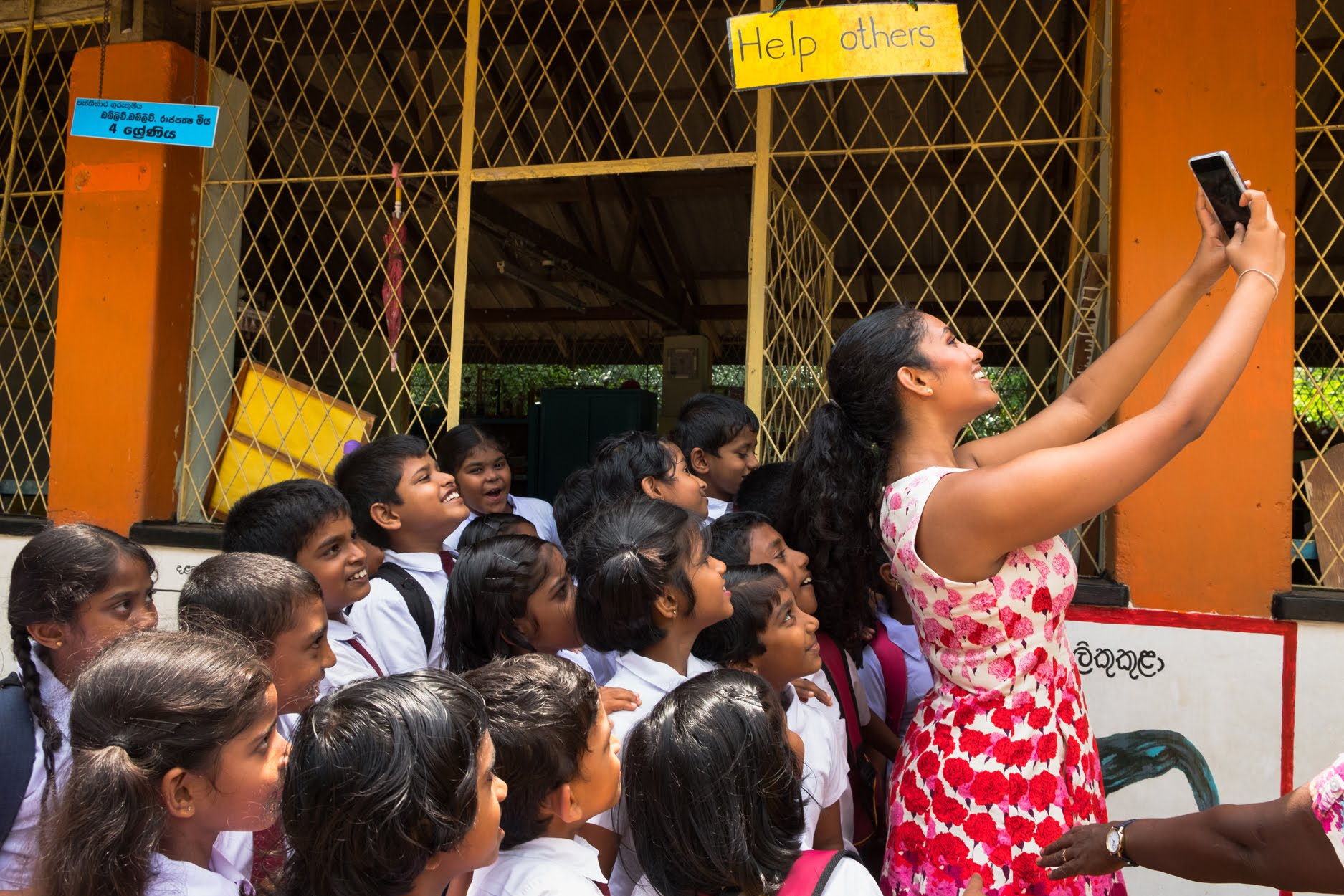 Palpita lower school students join Hiruni in a selfie outside in their courtyard that she will post to social media for Close To My Heart.