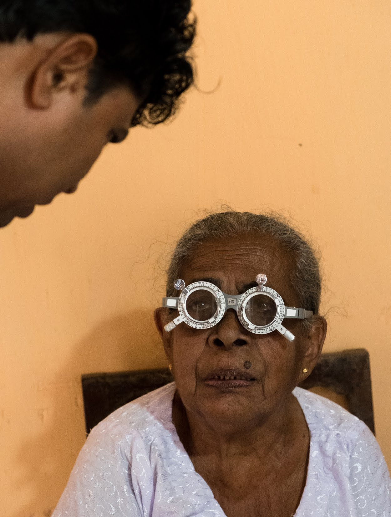 An elderly woman has her prescription gauged by Dr. Vitharana.