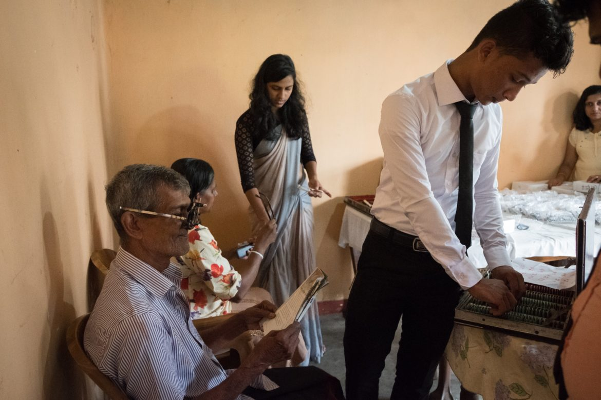 Uditha Chanaka, a young optometrist on the all-volunteer team, files through his case of lens equipment to test an older gentlemen's prescription for reading glasses. A great many elder Sri Lankans who lack access or resources to purchase glasses, will simply stop reading, potentially diminishing their ability to stay informed of current events, enjoy recreational reading, or decipher important mail and personal paperwork that they might need to understand.