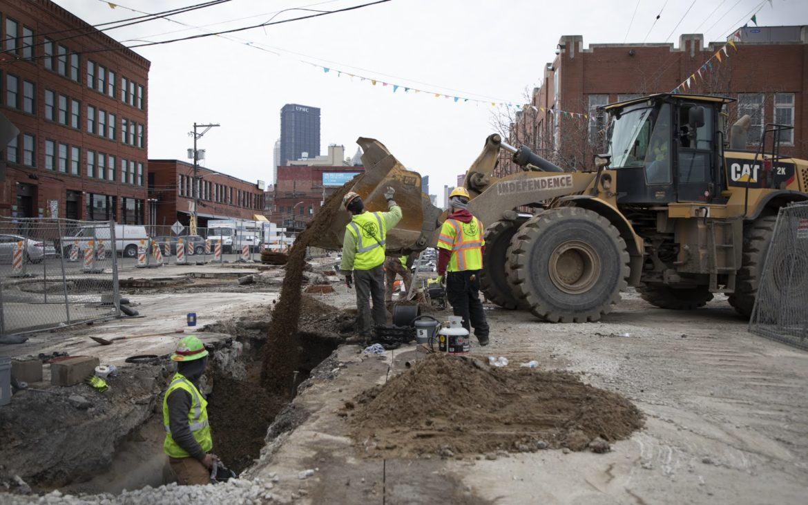 Construction workers pour dirt near the Produce Terminal in Pittsburgh's Strip District in late February 2019. (Photo by Kat Procyck/PublicSource)