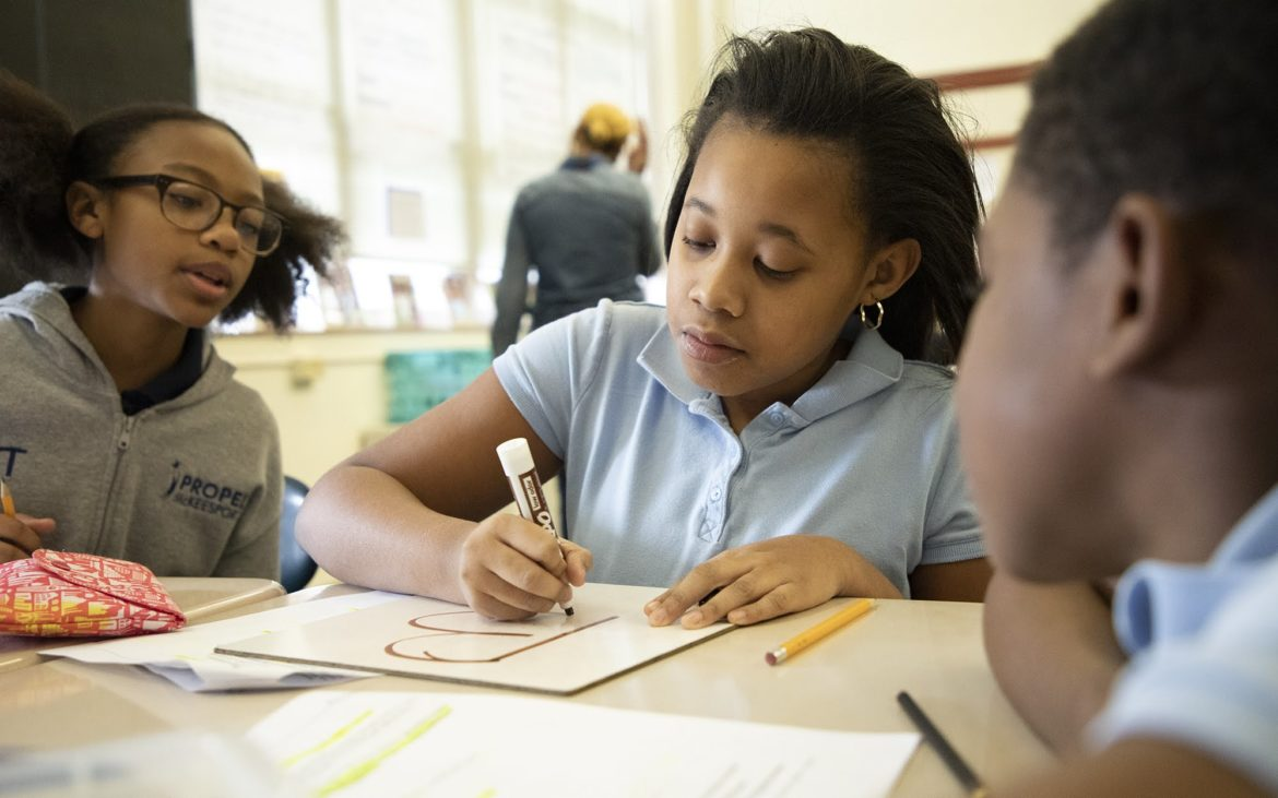 "Propel McKeesport fifth grader Phelicity Marion (center) works with group partners Ryenn Thomas (left) and Dijon Freeman (right) on a reading passage in their English language arts class. The group answered ""B"" to a multiple choice question posed by the teacher about the reading passage. (Photo by Kat Procyk/PublicSource)"