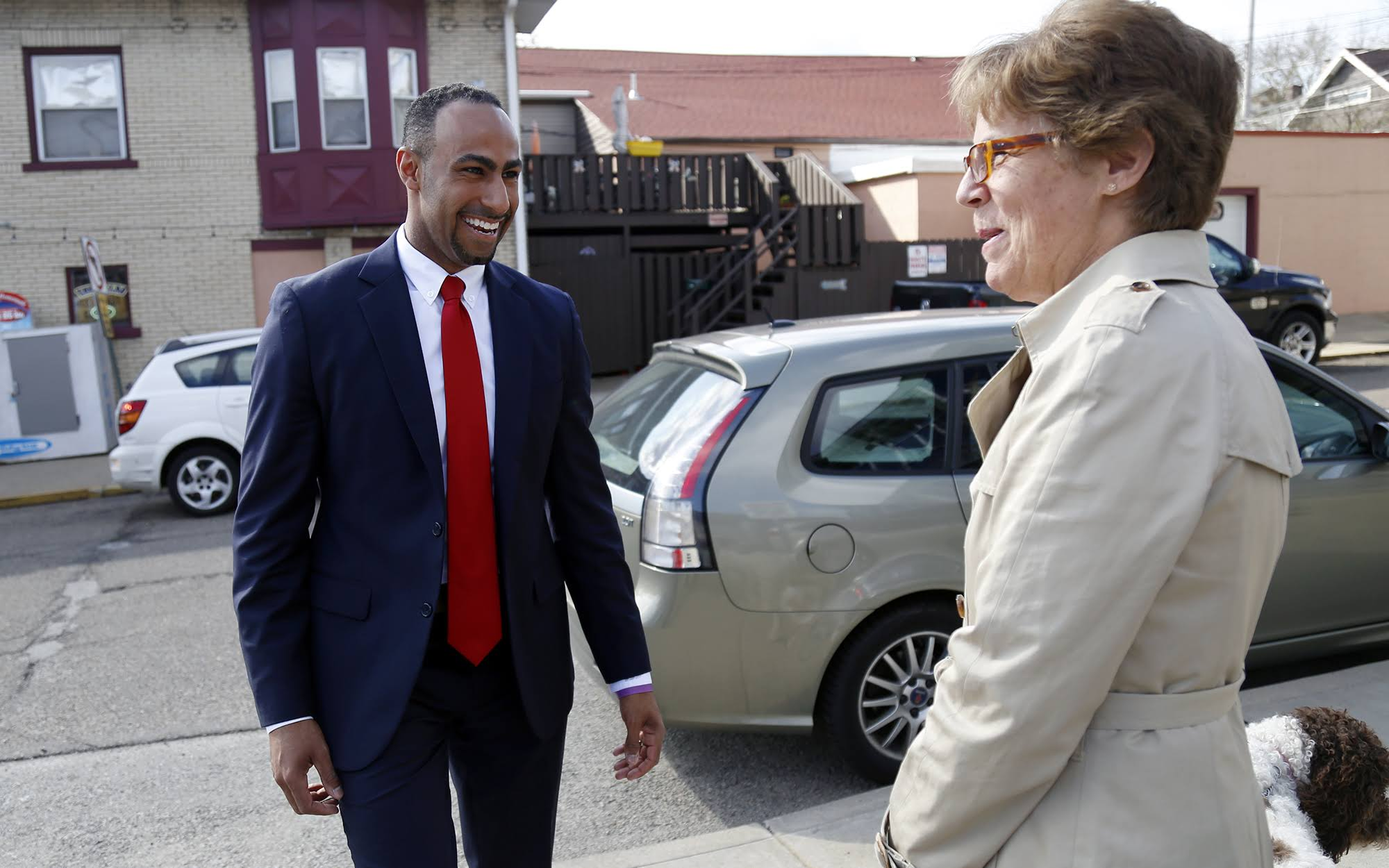 Gerald Dickinson chats with neighbor and colleague Mimi McCormick while walking in Regent Square. (Photo by Ryan Loew/PublicSource)
