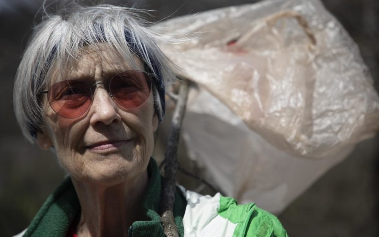 Ann Bristow protested outside the Marcellus and Manufacturing Development Conference in Morgantown on April 9, 2019. Bristow held a branch wrapped in plastic bags to represent pollution from the petrochemical industry. (Photo by Kat Procyk/PublicSource)