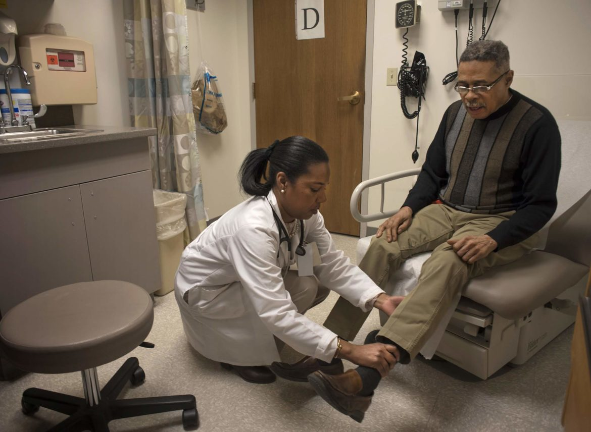 Dr Esa Davis checks William Miller Jr.' legs during at check up at UPMC Montefiore in Oakland. (Photo by Martha Rial)