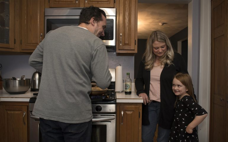 Katelyn's husband, Tony, tries to get his daughter, Vienna, to smile as he makes stir fry for family dinner at their McCandless Township home. (Photo by Martha Rial/Pittsburgh Magazine)