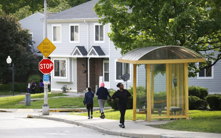 People walk along Johnston Avenue in Glen Hazel, near townhomes owned by an affiliate of the Housing Authority of the City of Pittsburgh. (Photo by Ryan Loew/PublicSource)