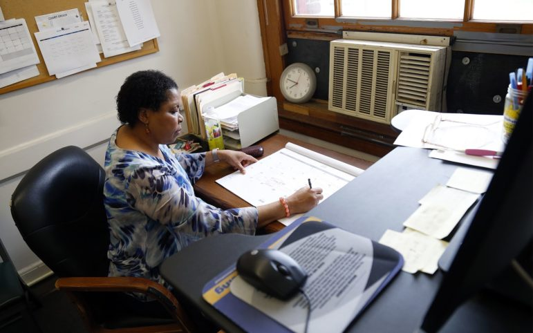 Zita Iwuoha checks her calendar in her office at the Allegheny County Health Department's Frank B. Clack Health Center in Lawrenceville, where she works as a public health nurse. (Photo by Ryan Loew/PublicSource)