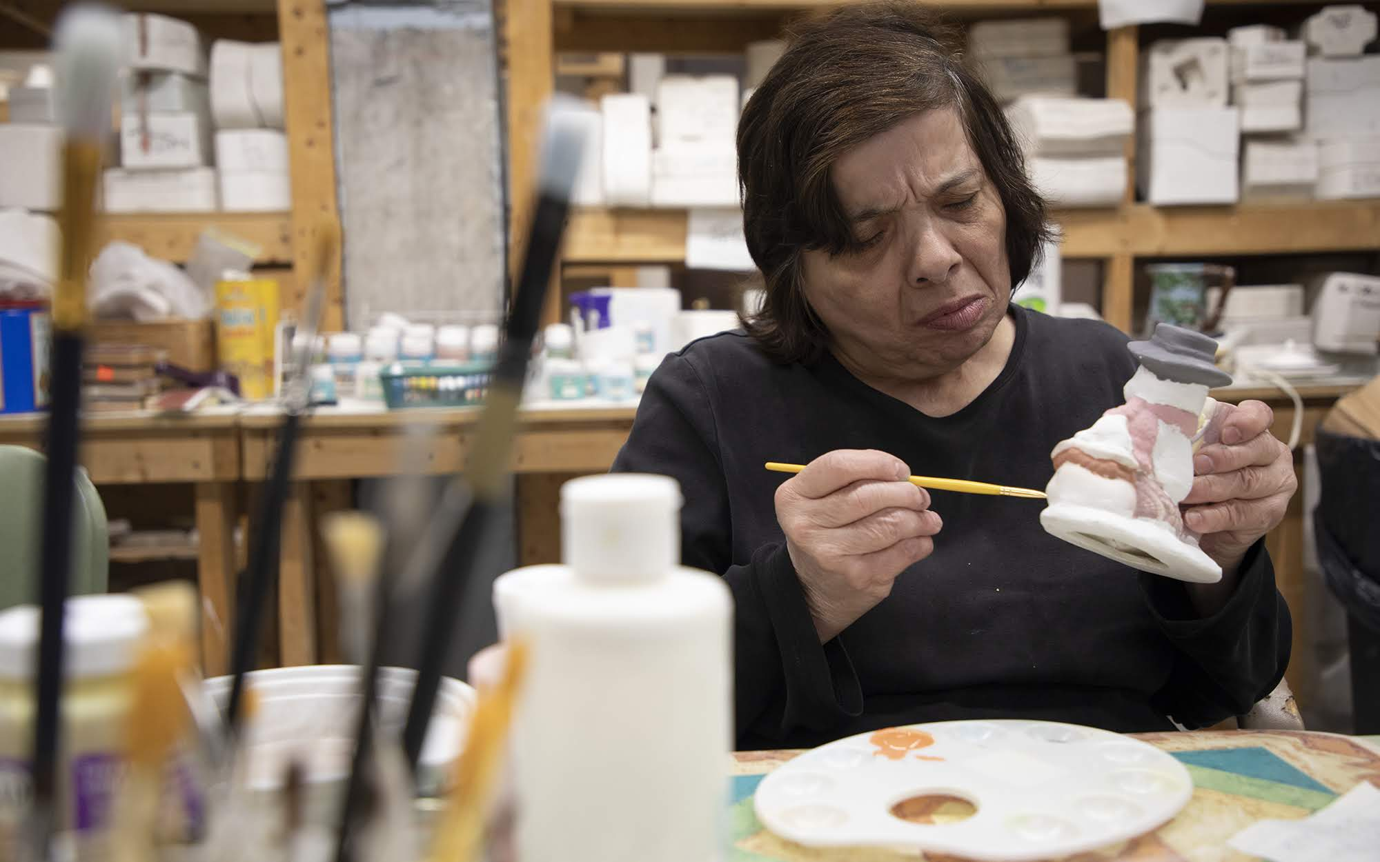 Janet Simeone paints a snowman in her ceramics class at Milestone Centers.